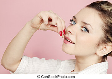 woman eats tablet against the pink background