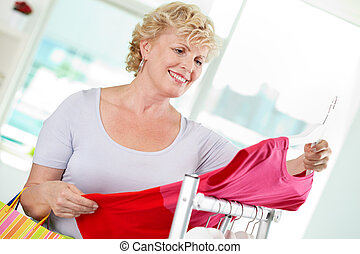 Shopper - Portrait of middle aged woman choosing new tanktop...