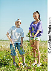 Mother and  teen boy planting tree