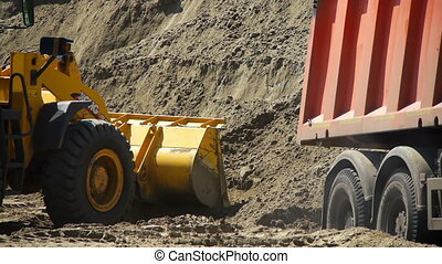 Red truck takes away the sand from the loading