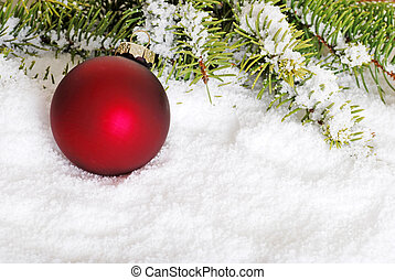 red christmas ball in snow with spruce tree branch
