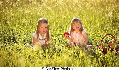 Two sisters eating apples