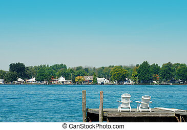 two adirondack chairs on a dock - two Adirondack chairs on a...