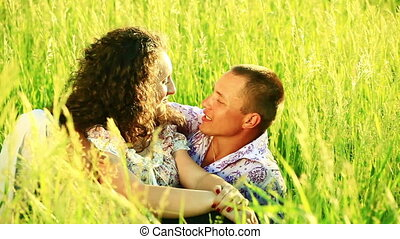 Happy young adult couple in grass