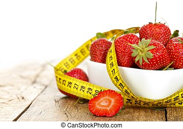 Diet - Closeup of a bowl with strawberries and a measure...