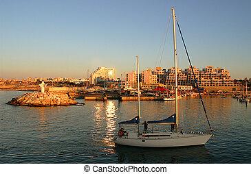 Yacht entering marina at sunset. - Yacht entering marina at...