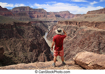 Grand Canyon hiker - a hiker standing on an overlook in the...