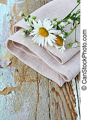 bouquet of daisies on the linen bag on a wooden table rustic...