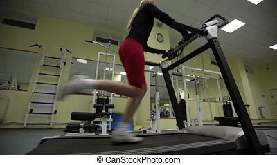 Working out - Young woman running on the training apparatus
