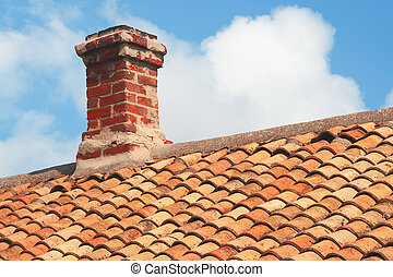 Tile roof with brick chimney against a blue sky