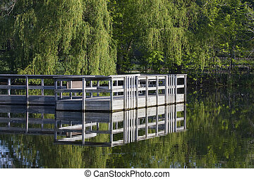 Boat dock sits in the middle of a pond.