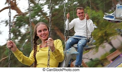 Couple in park - A young couple making fun on a carousel in...