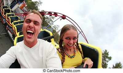 Entertainment - A young couple making fun on a coaster in...
