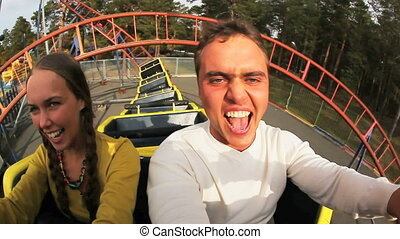 Couple on coaster - Two teenagers shouting while riding a...
