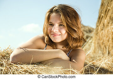 girl resting on  hay
