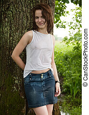girl in wet shirt near old tree during rain