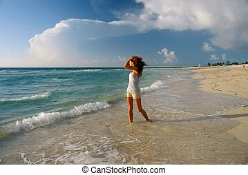 Young woman on the beach - Girl looking at rising sun on...