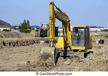Yellow digger at big job site - Yellow mechanical digger and...