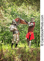 fighting knights  - Two knights in armor fights in forest
