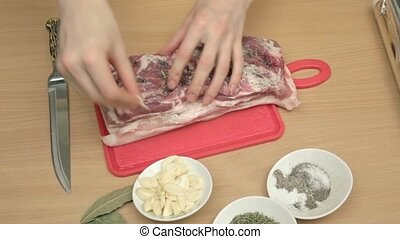 Tucking thin slices of garlic in sa - Young woman tucking...