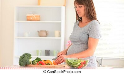 Pregnant woman preparing vegetables in her kitchen