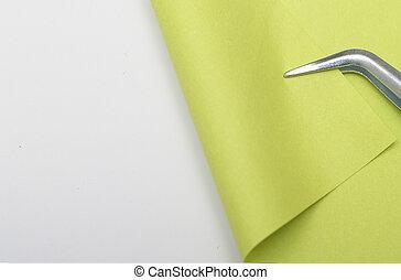 Bent - green piece of paper is bent tweezers