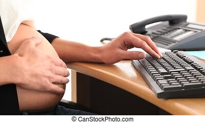 Pregnant office worker touching her belly while answering...