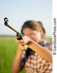 aiming girl - girl aiming a pneumatic rifle against field....