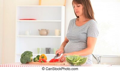 Happy pregnant woman cooking in her kitchen