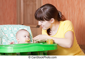 Mother feeding baby at home