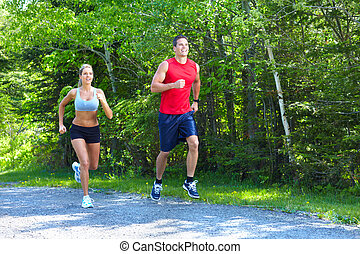 Jogging couple. - Young couple jogging in park. Health and...