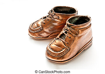 Babyshoes in bronze, on white background