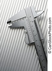 caliper - metal gauge closeup on a metal surface