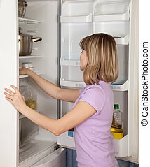 young woman looking in fridge - young woman looking for...