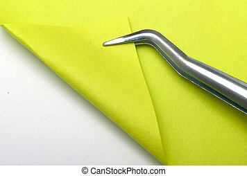 Bent - green piece of paper is bent tweezers