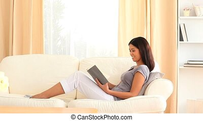 Young woman reading a book in her living room