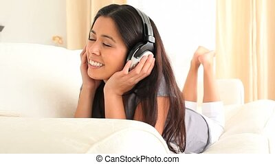 Cute woman enjoying some music in her living room
