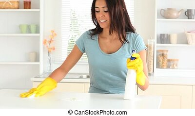 Young woman cleaning her kitchen with yellow gloves