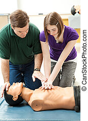 Teen Girl Practices CPR - Teen girl practicing CPR on a...