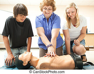 CPR Instruction in School - Teacher demonstrates CPR life...
