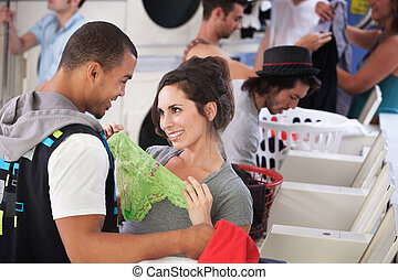 Romance In The Laundromat - Young lady holding underwear in...