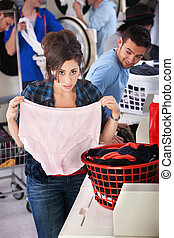 Woman Holding Granny Panties - Worried young lady holds...