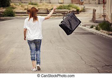 Young girl throws her suitcase walking down the street Rear...