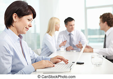 Secretary typing - Mature businesswoman sitting in office...
