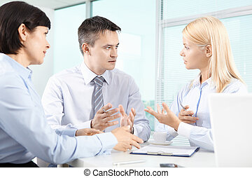 Discussion - Three business partners sitting in office and...