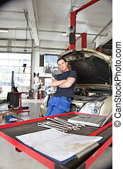 Auto Repair Shop - Focus on wrench and laptop while man...