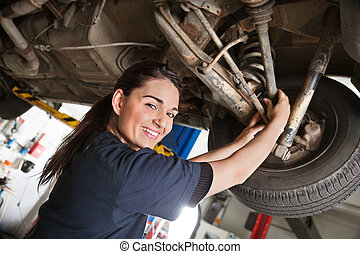 Portrait of smiling young female mechanic inspecting a CV...