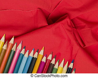 Colour pencils on a red tissue background