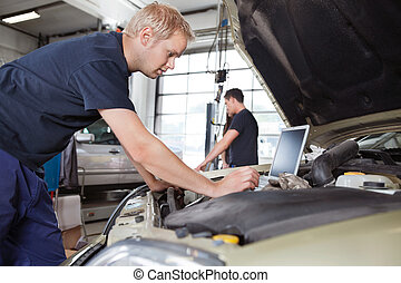 Mechanic using laptop while working on car with people in...