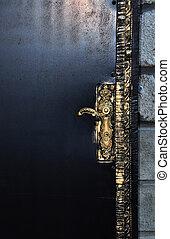 Black door with golden doorhandle.